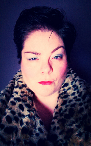 image of me with short, punky hair and colorful makeup, sneering with one raised eyebrow, wearing a faux leopard coat and standing against a purple wall