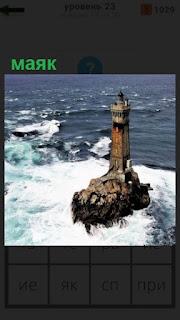 стоит в воде среди волн на небольшом островке маяк