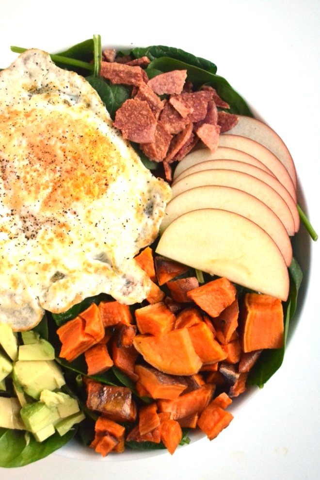 Breakfast Salad with Warm Maple Vinaigrette is a unique salad with baby spinach, roasted sweet potatoes, chopped sweet apples, crumbled bacon, creamy avocado and runny eggs! www.nutritionistreviews.com