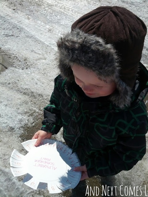 Child marking off letters on a paper plate scorecard as part of an outdoor alphabet scavenger hunt
