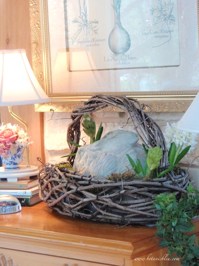 A rustic grapevine basket holding a concrete bunny shows how texture makes the difference in vignettes