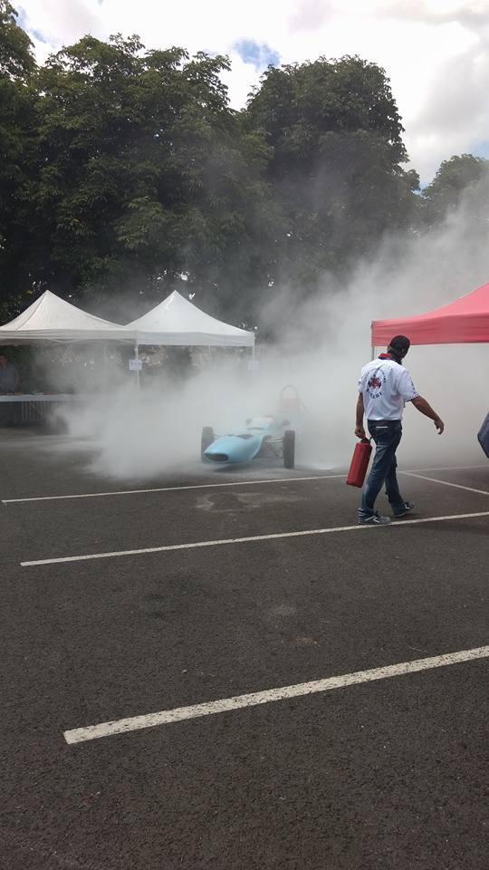 une voiture ancienne vintage de course avec le moteur en feu