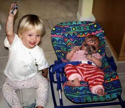 Hermanita pintando a su hermanito bebe