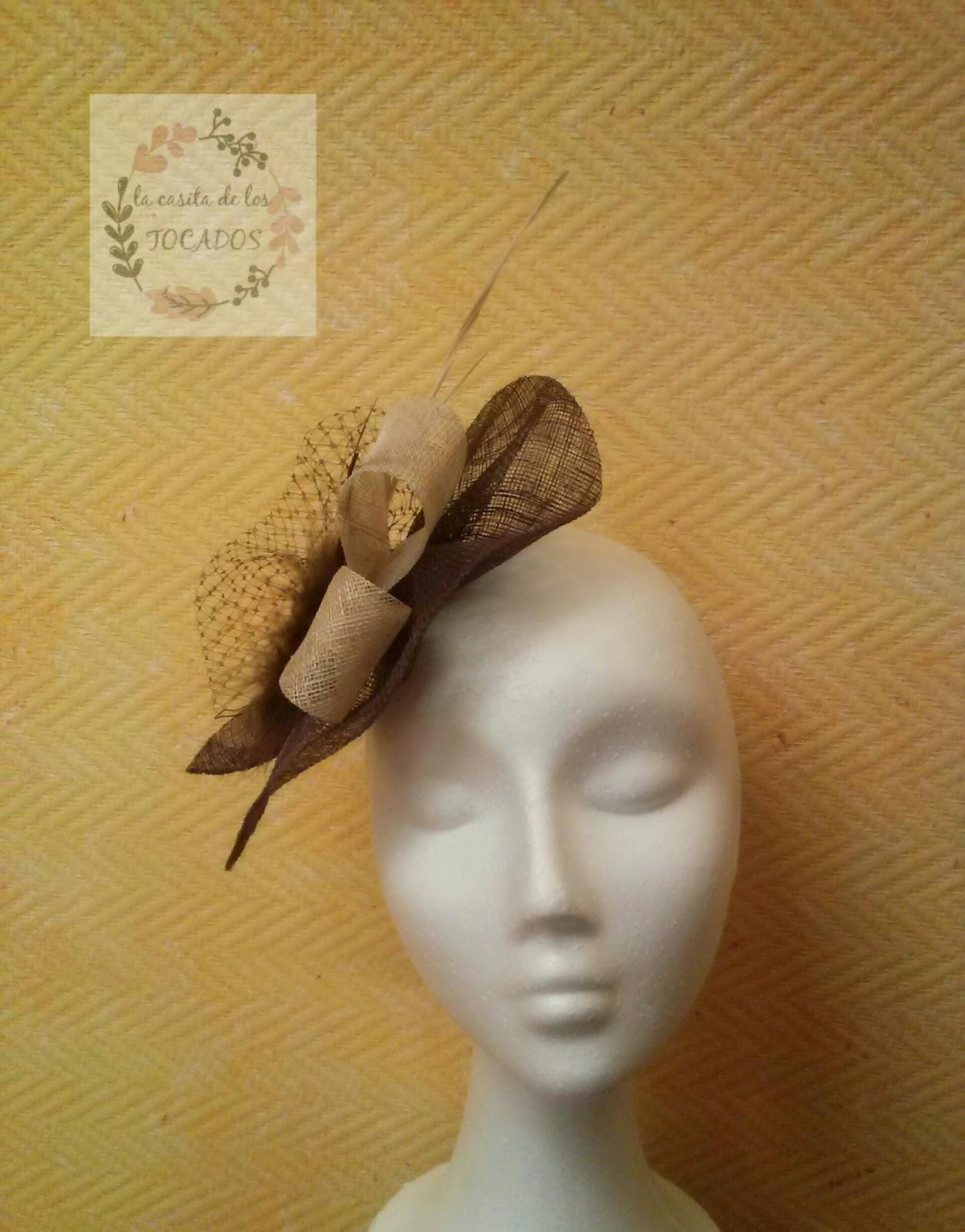 tocado de sinamay en color marrón, combinado con beige, con plumas variadas, incluido marabu y velo