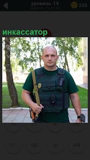 На улице в форме стоит мужчина инкассатор с оружием и спец. средствами