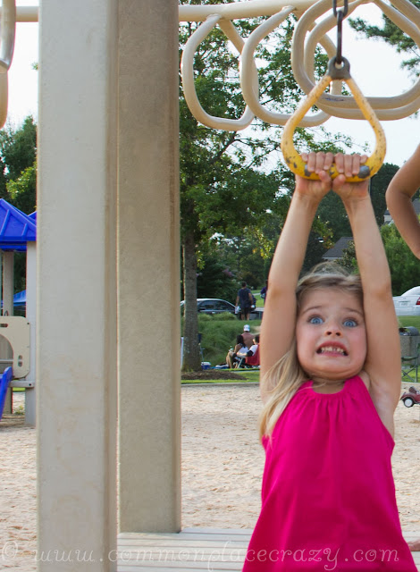 Little girl with big eyes frightened on the playground zip line