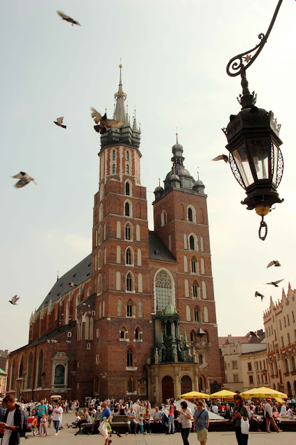 Pigeons flying overhead a crowd of people leisurely strolling in front of a red brick Basilica.