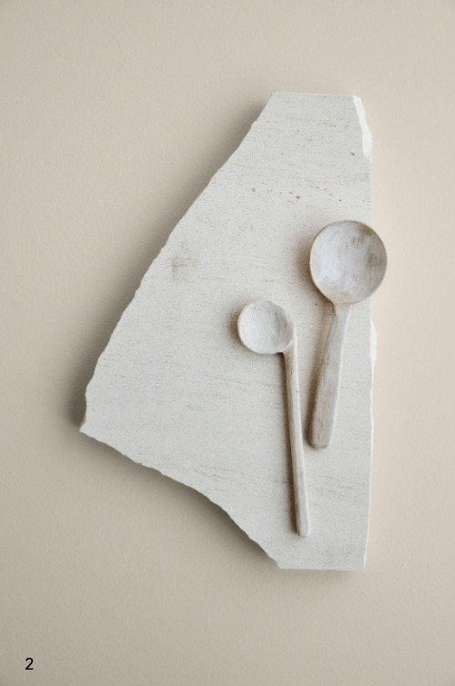 Holzlöffel liegen dekorativ auf hellem Stein