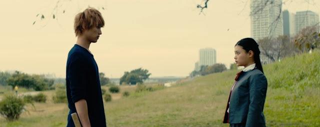 Ichigo camiseta azul, pelo teñido de naranja y despeinado frente a Rukia uniforme gris con camisa blanca y lazo rojo, perfectamente peinada se miran a las afueras de una ciudad
