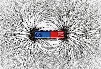 Bir mıknatıs ve demir tozu içinde belli olan manyetik alanı