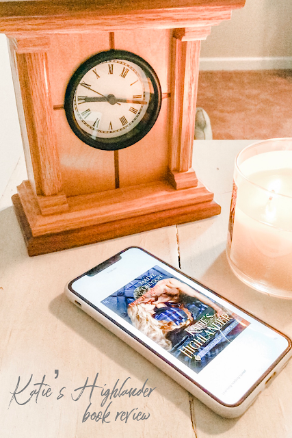 Katie's Highlander book, clock and candle on a white table