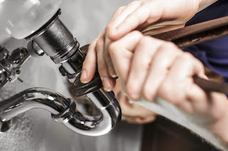 A plumber repairing a bathroom pipe