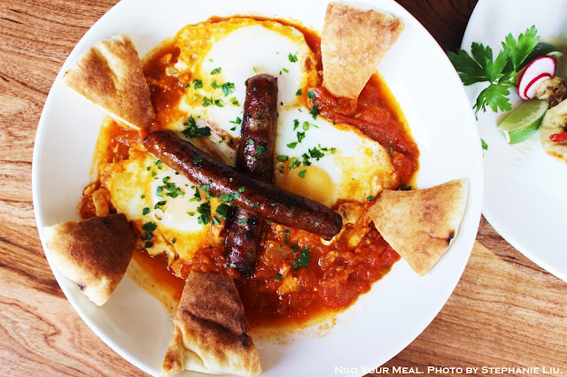 Shakshuka Moroccan Breakfast: three eggs baked with tomato, onion, pepper, spices, tahini, pita, and merguez sausage at Mémé Mediterranean