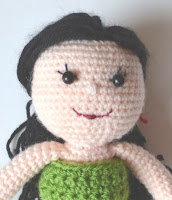 Head and shoulders of Kwokkie Doll wearing a green bandeau style bikini top.