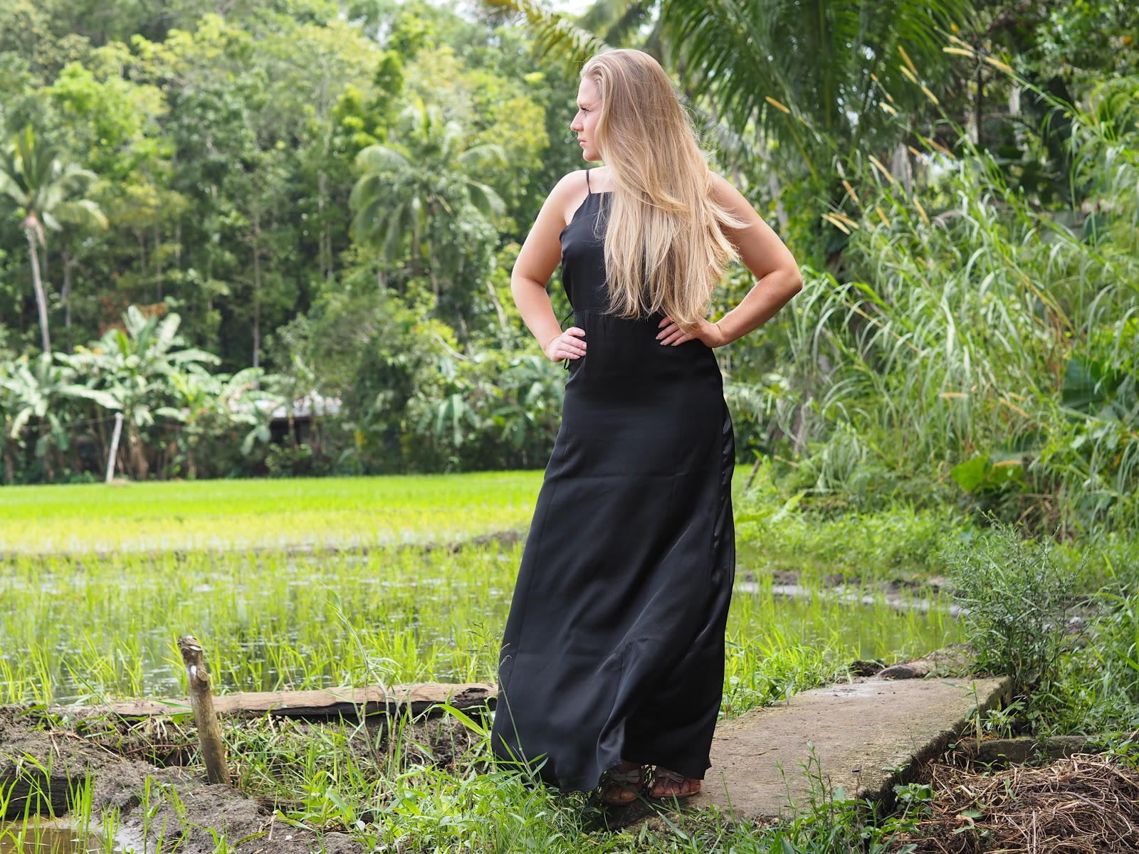 Blonde girl wearing Black Boohoo dress in rice fields in Philippines