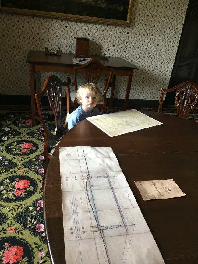 toddler-pouting-and-sat-at-grand-table-with-fantastic-drawings-of-boats