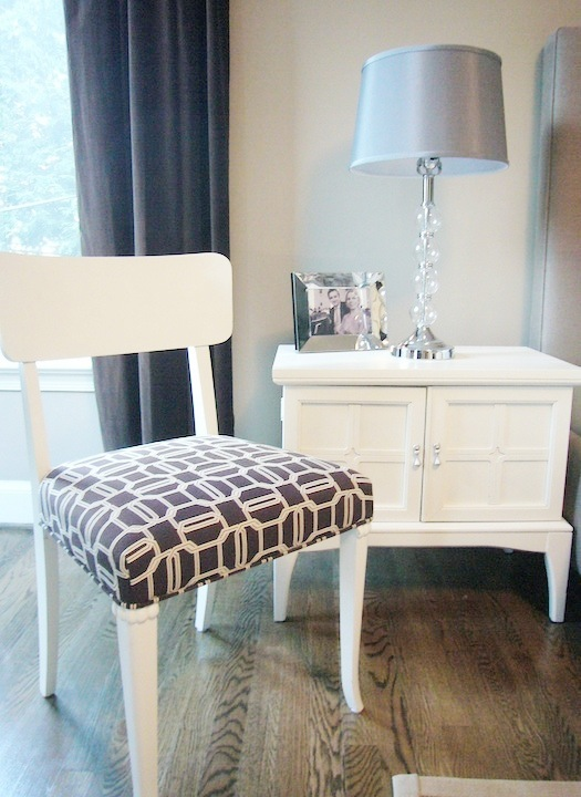 The side chair painted bright white and upholstered with Kelly Wearstler's brown Emerald Cut fabric on the seat in a bedroom with a hardwood floor, grey curtains, white nightstand with a framed photo and a lamp with a glass base