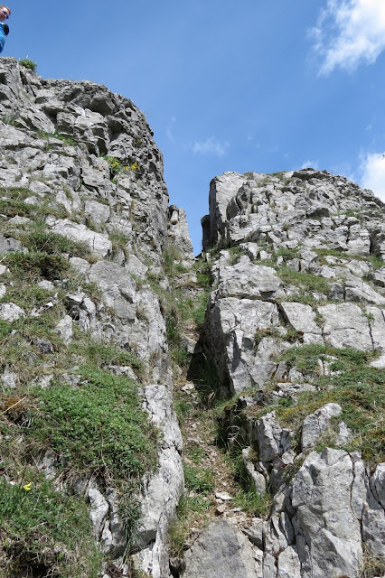 A narrow cleft in the rock, providing a scrambling access to the top of the outcrop.