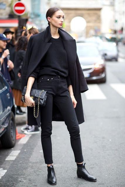 Девушка в черных джинсах и черном пальто