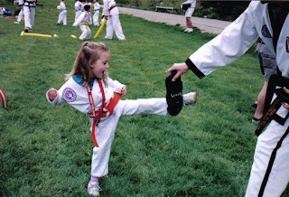 Martial arts girl kicking a target