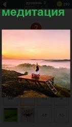 на берегу моря на постаменте человек занимается медитацией