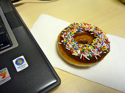 doughnut with chocolate icing and rainbow sprinkles beside a laptop