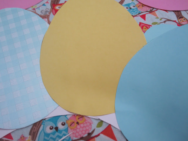 The card eggs being layered and glued on the paper plate