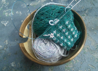The cuff of a mitten done in green and white colourwork.  The knitting is on top of both yarn balls resting in a yarn bowl.  The front of the work is facing, and you can see a set of live stitches in the contast colour where the intarsia has begun.