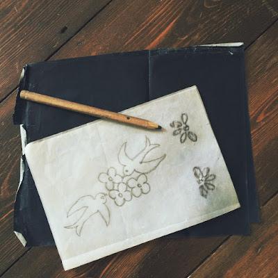 Papier calque sur lequel on a tracé deux colombes qui picorent des fleurs