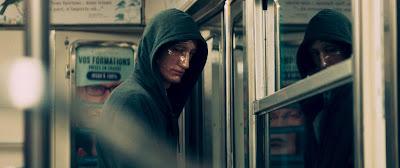 """L'illustration représente une scène du film """"Sauver ou périr"""" dans laquelle Pierre Niney, qui incarne le sergent Pasquier se tient debout dans le métro avec un masque sur le visage et une capuche sur la tête."""