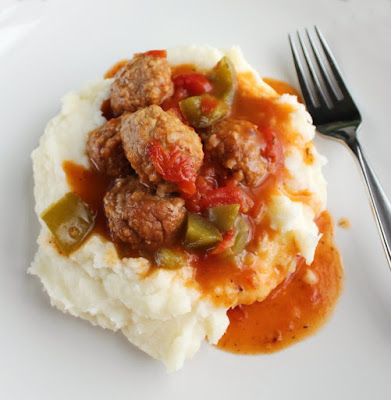 pile of mashed potatoes with swiss steak meatballs, peppers and tomato gravy