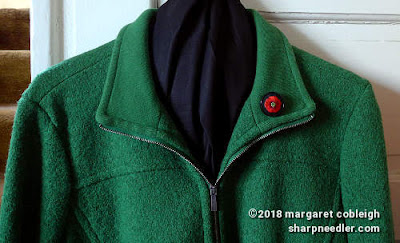 Embroidered remembrance poppy mounted in a silver pin setting pinned to green wool jacket