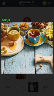 Стоят две чашки с чаем и на доске разлито немного меда