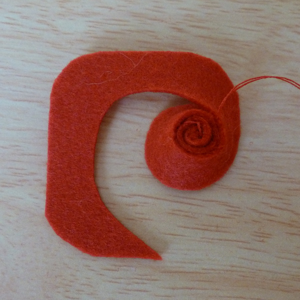 Red felt being rolled up to make a craft flower embellishment