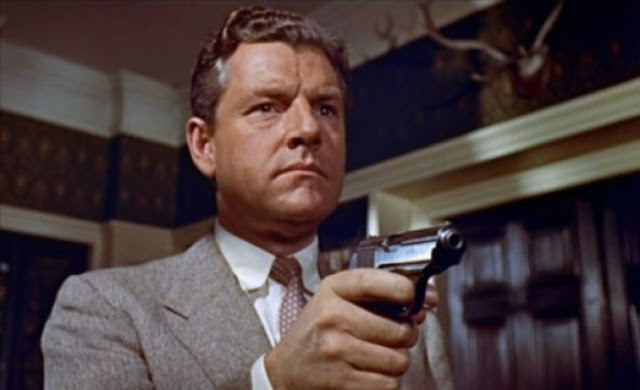 Kenneth More as Richard Hannay in The 39 Steps, pointing a gun