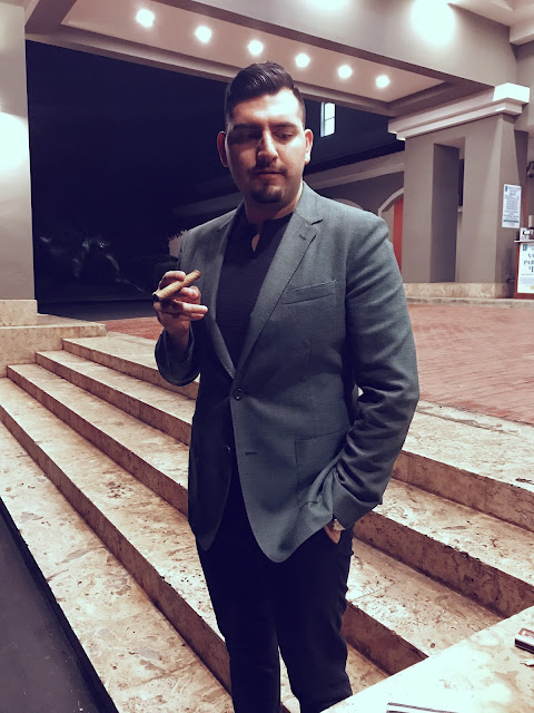 Grey full suit style in luxurious hotel while holding a cigar.