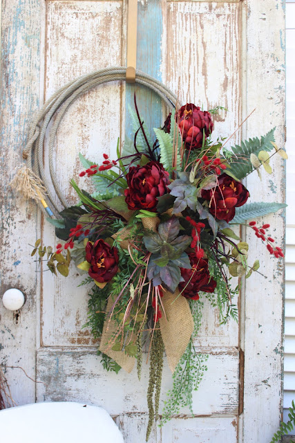 red rope wreath with burlap bow