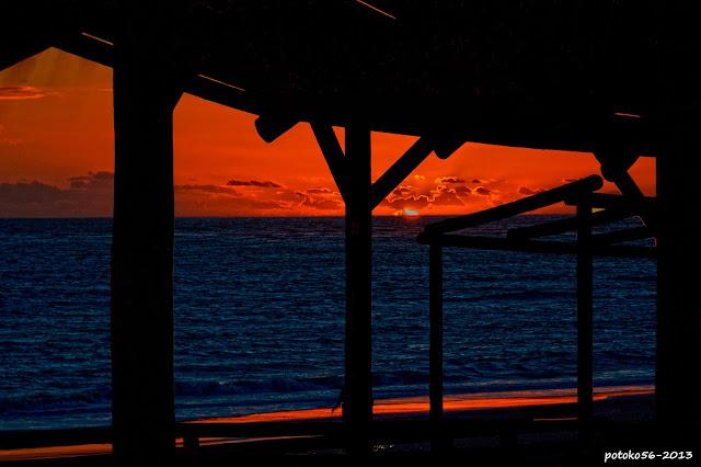 Fotografía de atardecer rojo fuego en la playa