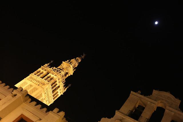 Fotografía nocturna de la parte superior de la  Giralda de Sevilla junto a la luna