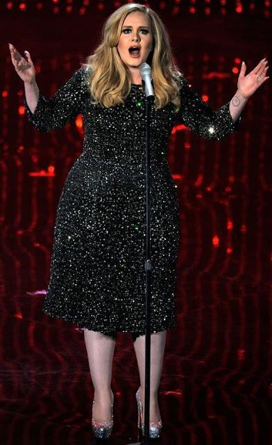 Adele cantando en concierto y de cuerpo entero