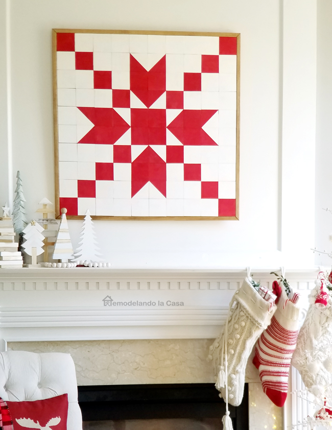 red and white mantel with wooden trees and knitted stockings