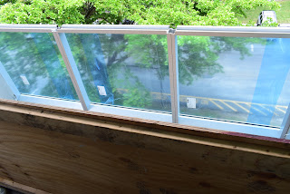 image of small balcony with concrete ledge removed and replaced with Glass ledge.