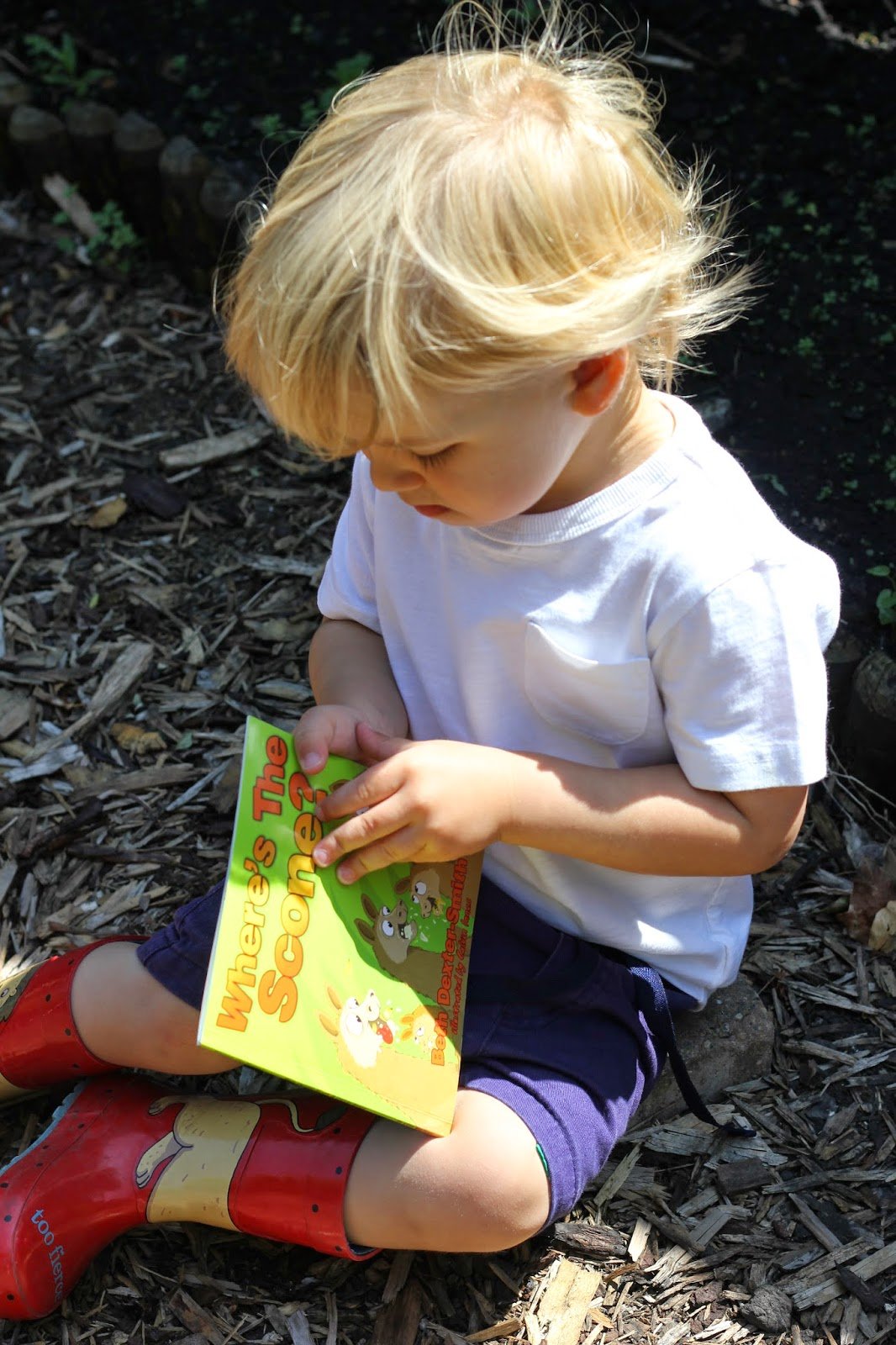 toddler reading in garden
