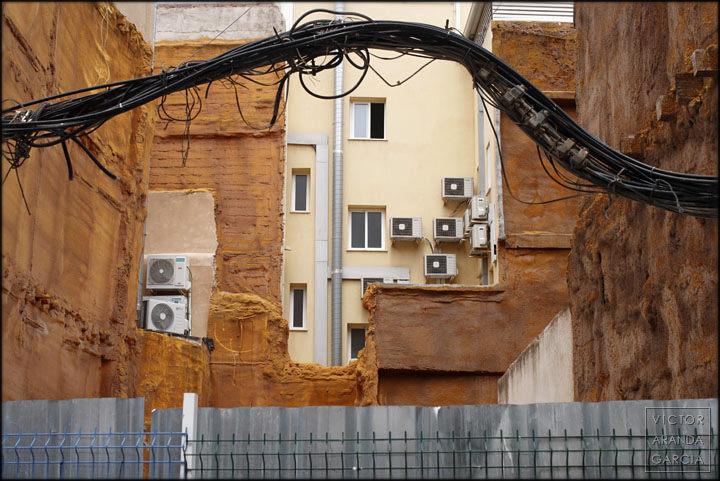 Fotografía del patio de un edificio con aparatos de aire acondicionado y ventanas enmarcados por cables y una valla