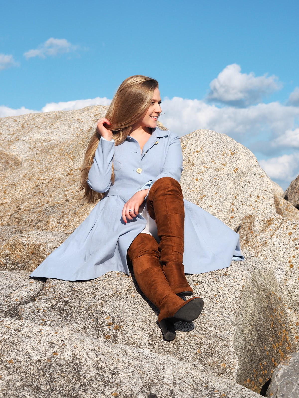 Blonde girl wearing blue coat and brown boots sitting on rocks at the beach