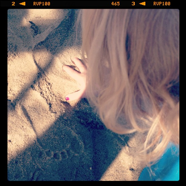 toddler hand and footprint in the sand