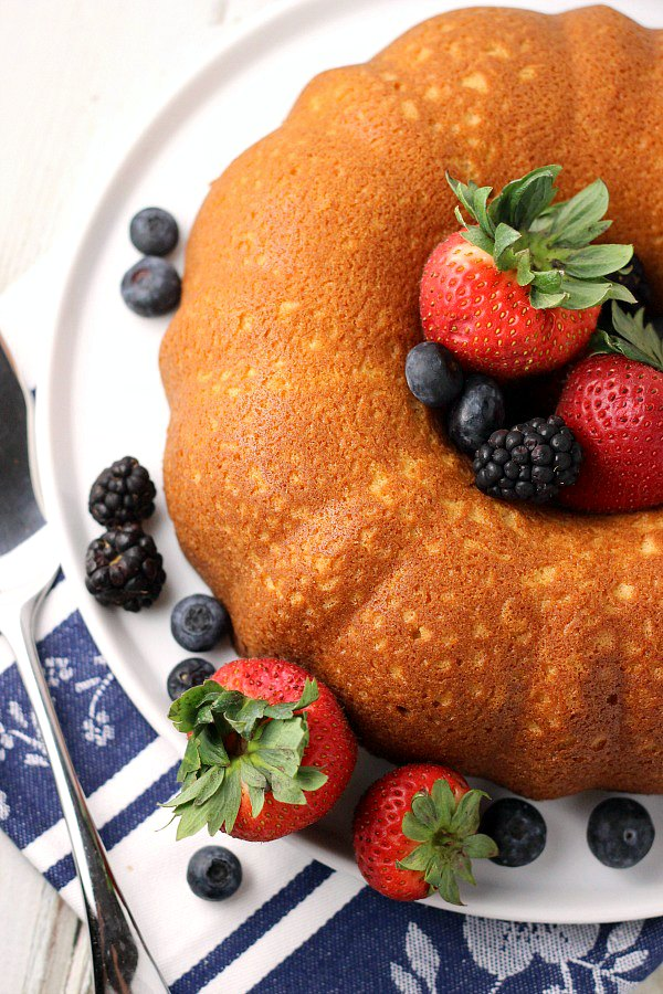 Overhead view of whole Buttermilk Pound Cake on white cake plate, surrounded by blueberries, strawberries, and black berries with server to the side