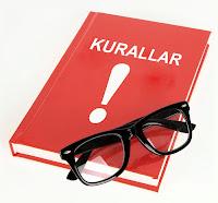 Üzerinde siyah bir gözlük olan kırmızı kurallar kitabı