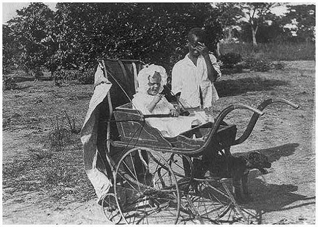 White child in baby carriage attended by black boy. ca. 1924.