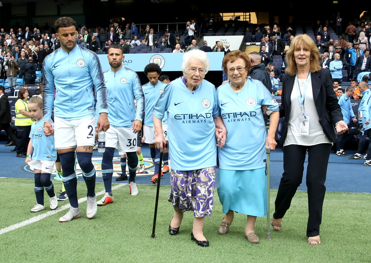 Manchester City fan Vera Cohen walks onto the Etihad pitch with sister Olga Halon